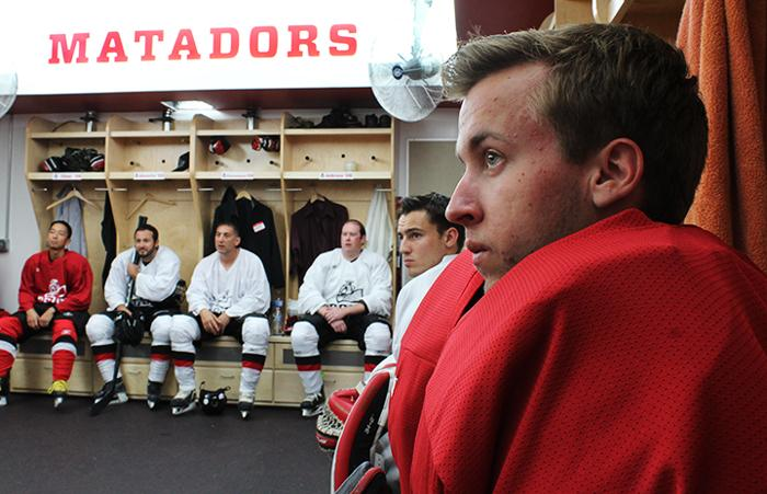 Six CSUN ice hockey players listen to coach as they prepare for a hockey game to begin.