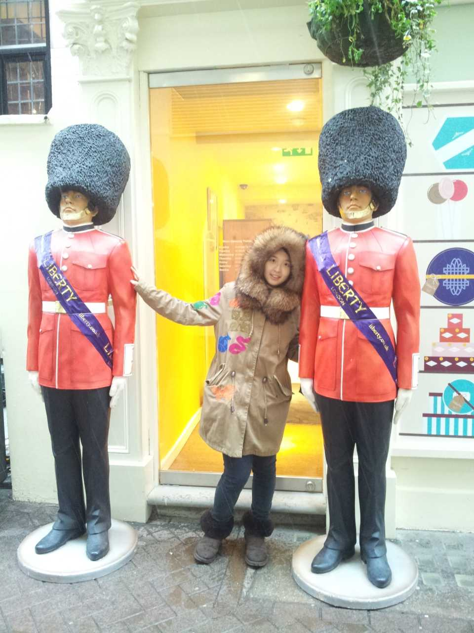 Tourist poses with two guard statues outside of a tea shop.