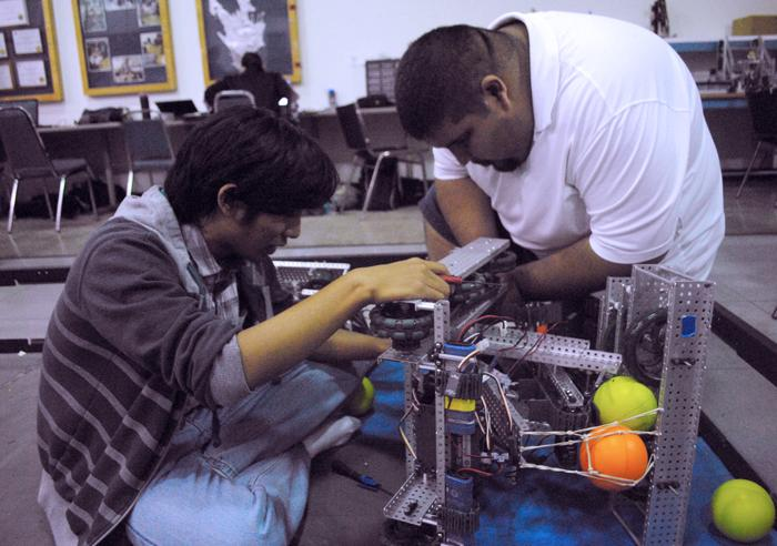 CSUN students works with associate to work on their robot in preparation for their robot club on Cal State Northridge campus.