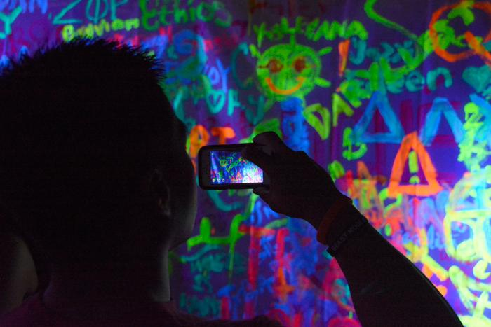 Student takes picture of neon wall at BIg Show.