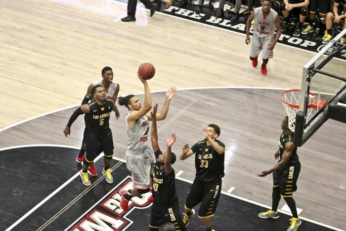 CSUN basketball player attempts to shoot basketball while teammate blocks members from opposite Cal State LA team.