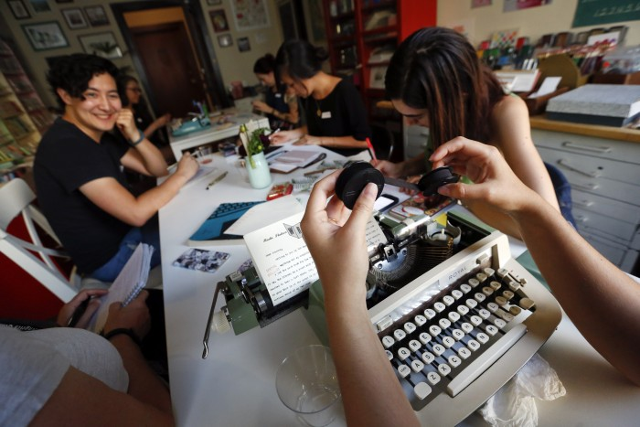 Margaret Haas, right, changes the ribbon on her typewriter as she types a letter to a penpal in Chicago during the monthly gathering of the L.A. Penpal Club at Paper Pastries Atelier in Los Angeles on Sept. 9, 2015. (Mel Melcon/Los Angeles Times/TNS)