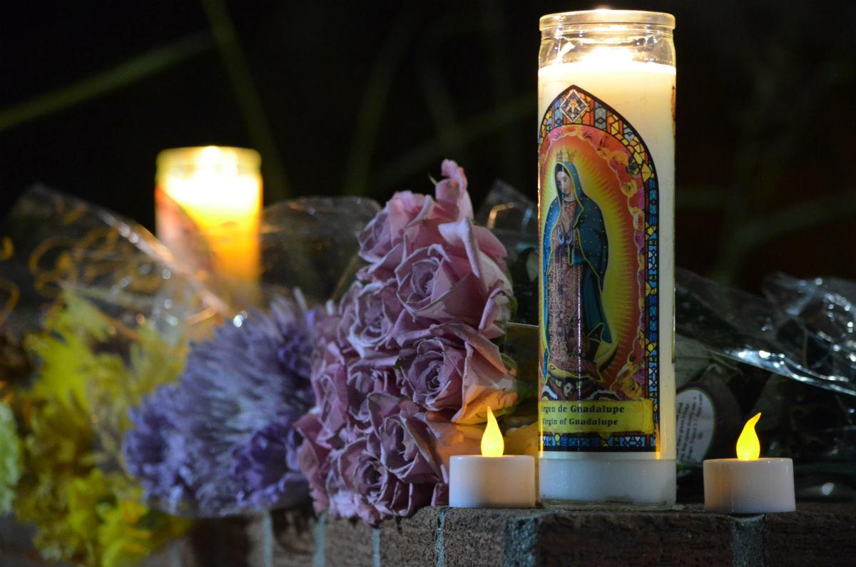 A memorial taking place at CSU Long Beach depicts several candles and flowers in remembrance of Nohemi Gonzalez.