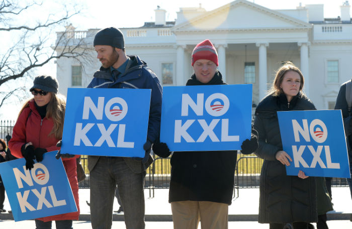 "Protestors stand outside of the White House holding signs that read ""No KXL"""