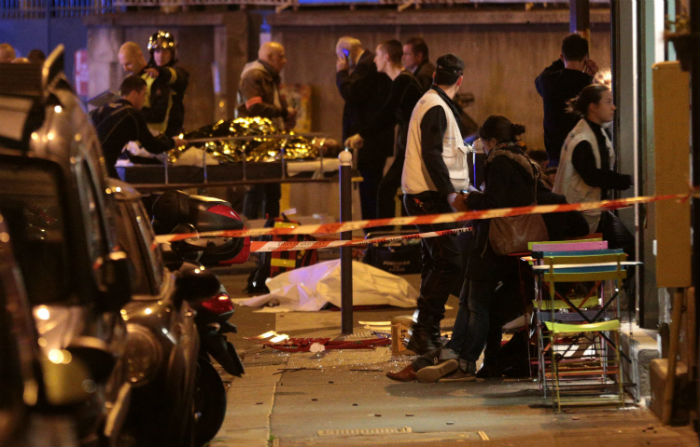 Medics stand by victims in a Paris restaurant on Nov. 13, 2015, after a reported shootout. (Maxppp/Zuma Press/TNS)