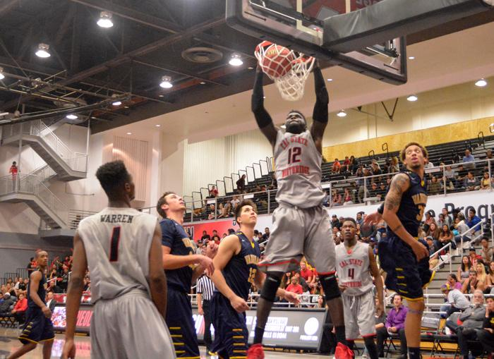 Senior Olalekan Ajayi puts down the two handed dunk to get 2 of his 17 points along with 10 rebounds to help the Matadors win their home opener game vs Vanhuard by a score of 52-71 on Wednesday, Nov. 18, 2015. (Silvia Aguilar / Contributor)