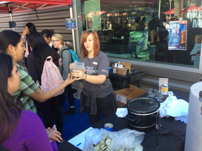 USU staffer Lea Morgan handing out hot wax to students to make their own candles.