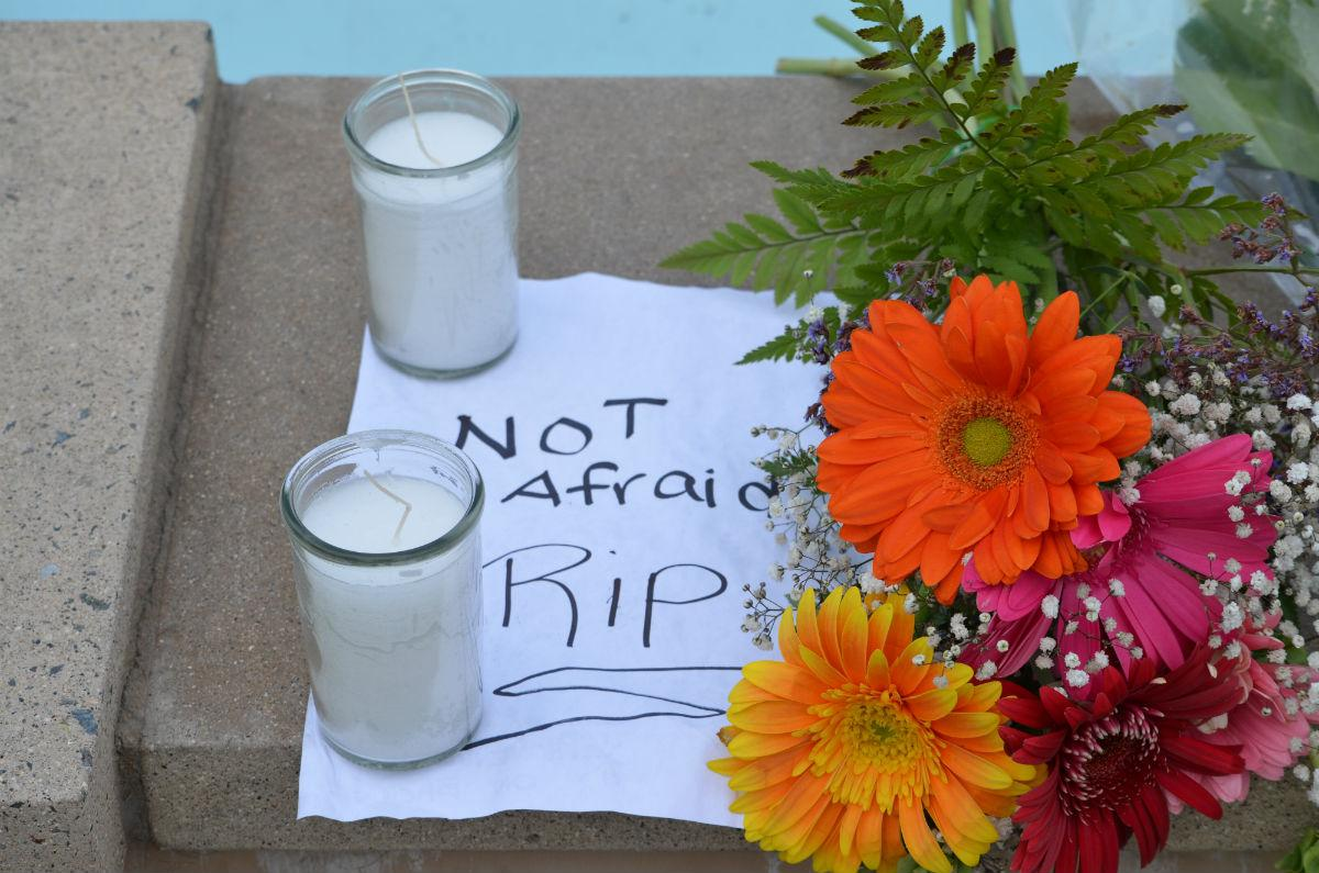 "Flowers, candles and a note that reads, ""Not Afraid RIP"""