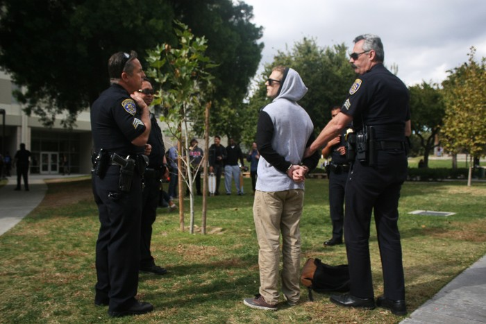 Surrounding police officers arrest CSUN student after attempting to kiss Ysidro Mensoza .