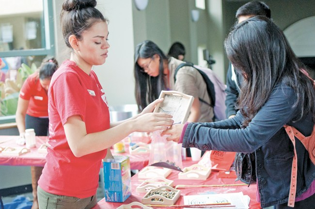 Perla Palacios, 21, Recreation & Tourism Management junior, right, help a student pour sand into the bag for safe keeping while taking a personal sandbox away to relieve stress at home while attending the Crunch Time event where students can release their stress a week before finals held at the USU Grand Salon on Tuesday, May 6, 2014 in Northridge, Calif. (Photo Credit: David J. Hawkins/Photo Editor)