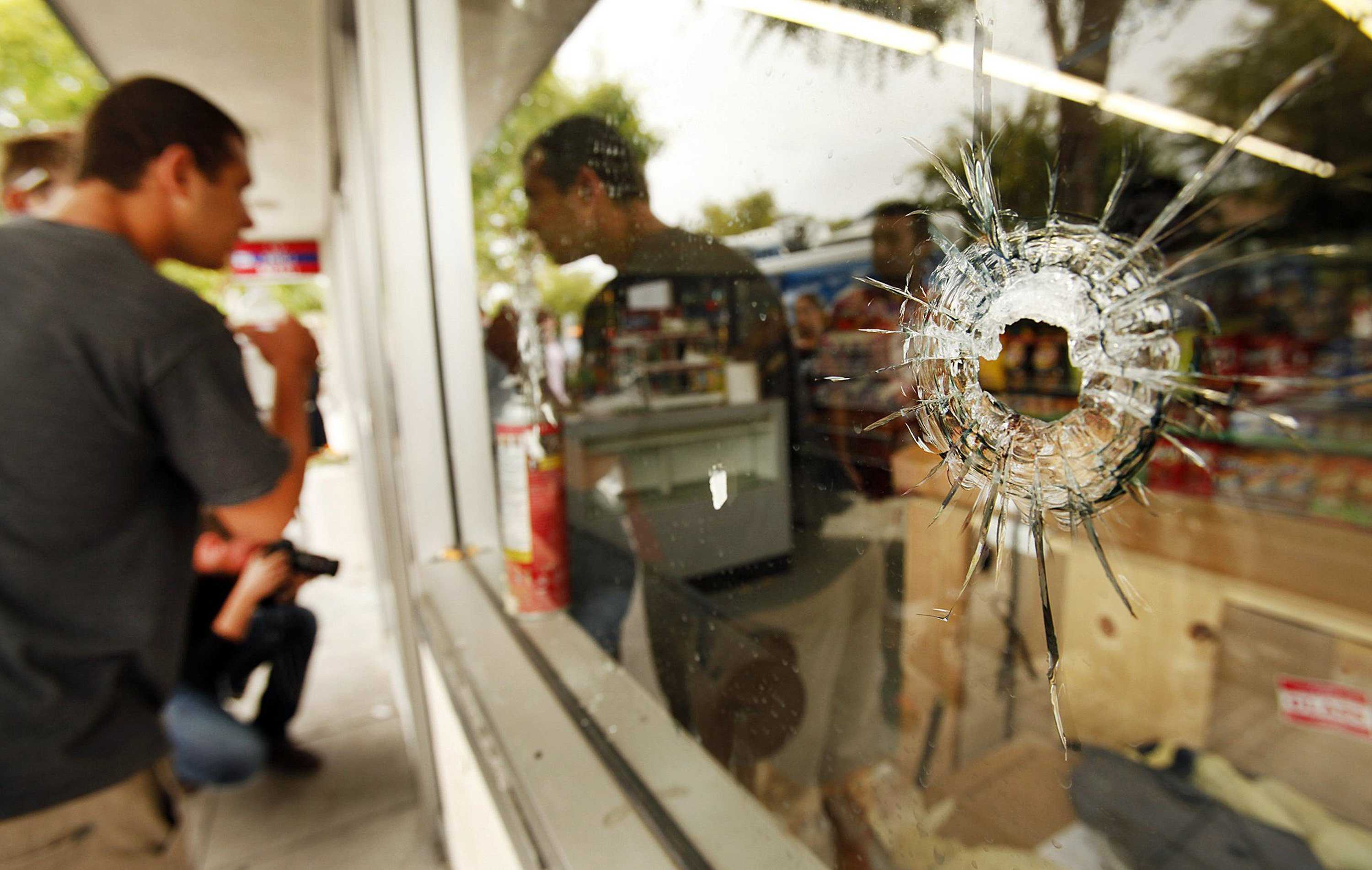 Students look through a window marked with bullet holes at the IV Deli in the Isla Vista neighborhood of Santa Barbara, Calif., Saturday, May 24, 2014. A shooting rampage on Friday left seven dead near the University of California, Santa Barbara. (Al Seib/Los Angeles Times/MCT)