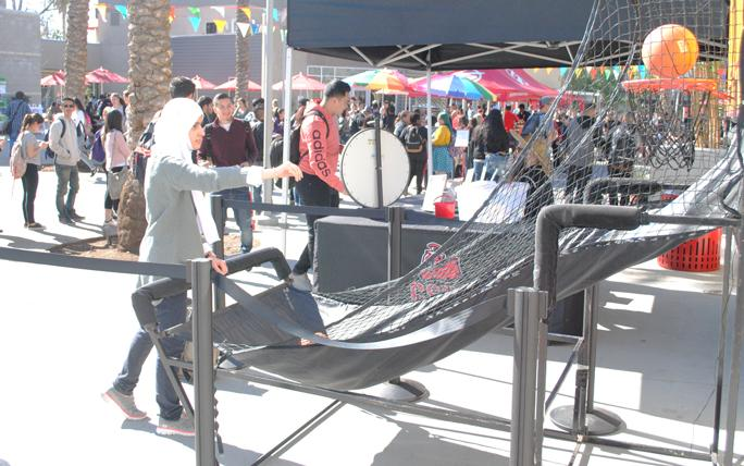 Fatemah+Alamar%2C+a+CSUN+engineering+major%2C+tosses+a+basketball+at+one+of+the+Spring+Kick-Off%27s+games+booths.