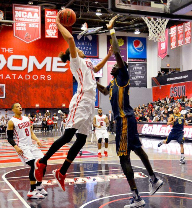 """Senior Tre Hale-Edmerson gets by with a dunk against UC Irvine's Mamadou Ndiaye's 7'6"""" defense in the first half of the game at The Matadome. (Patricia Perdomo / The Sundial)"""