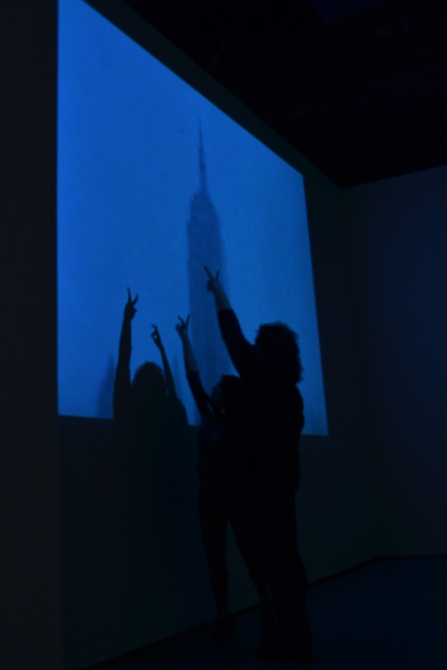 "Freshman Psychology major Johanna Wong, 18, and Freshman journalism major Giselle Pernett draw shadow puppets over an excerpt of Warhol's ""Empire."" (Eric Licas /The Sundial)."