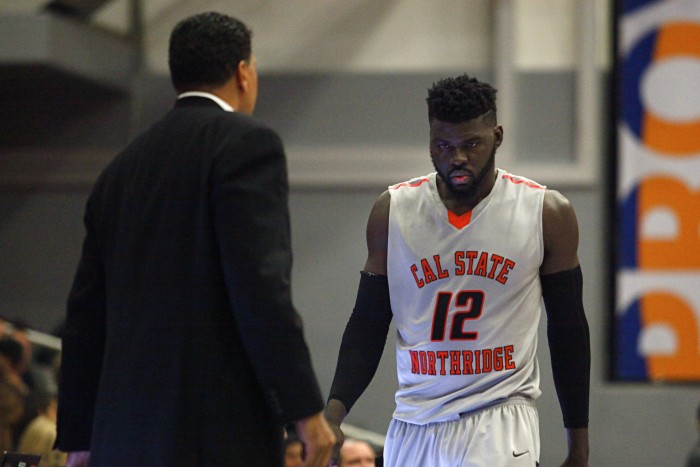 CSUN men's basketball head coach Reggie Theus stares at Olalekan Ajayi as he walks off the court against Cal State L.A. on Nov. 5, 2015. (File Photo / The Sundial)