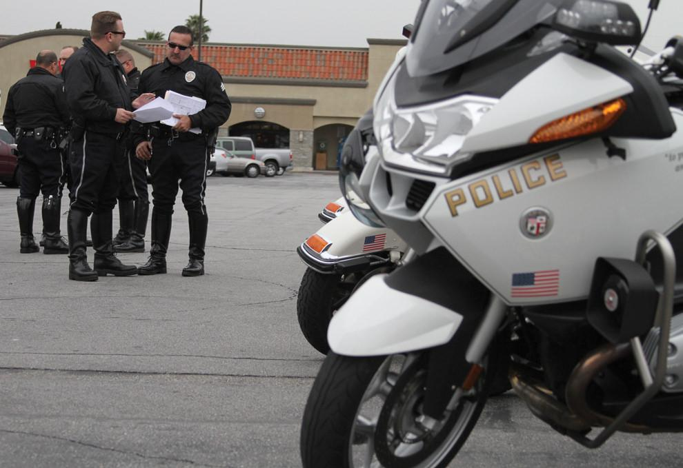 Police officers stand near police issued motorcycle
