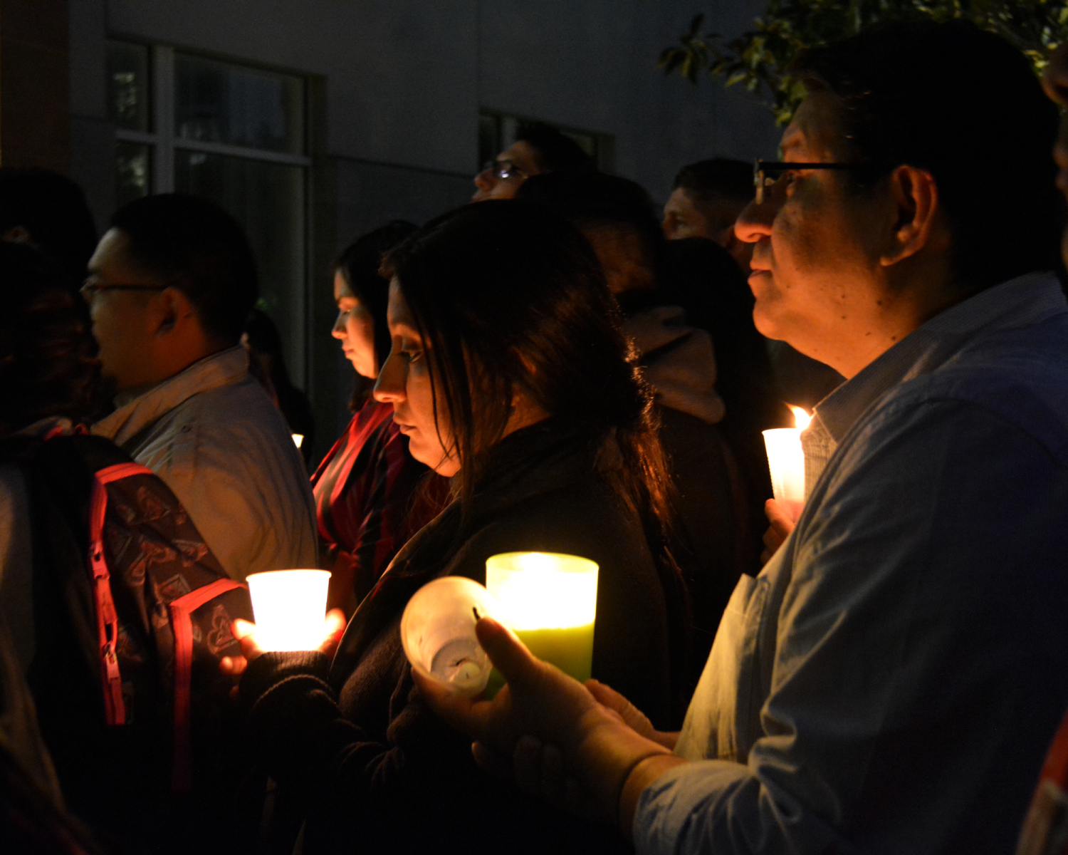 Crowd holds candles in hand during vigil