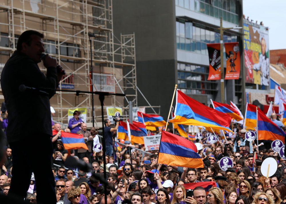Large crowd of people stand together and wave flags for recognition of Armenian Genocide