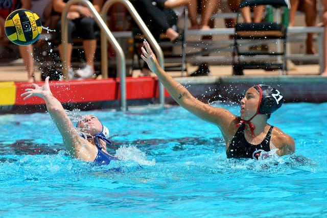 Two opposing water polo athletes play in pool