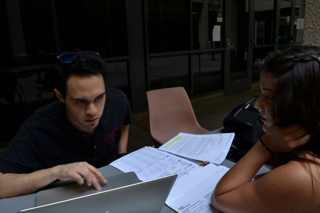 Two students sit across one another while working on a laptop