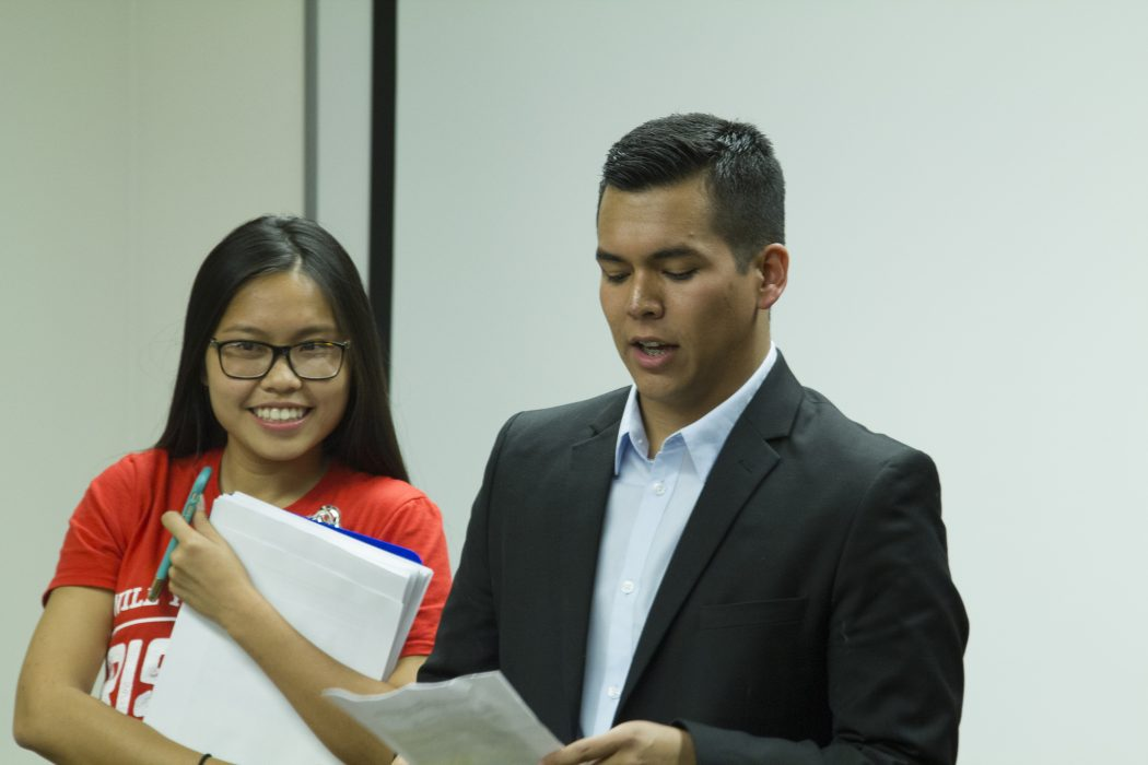 Two students carry papers as they talk