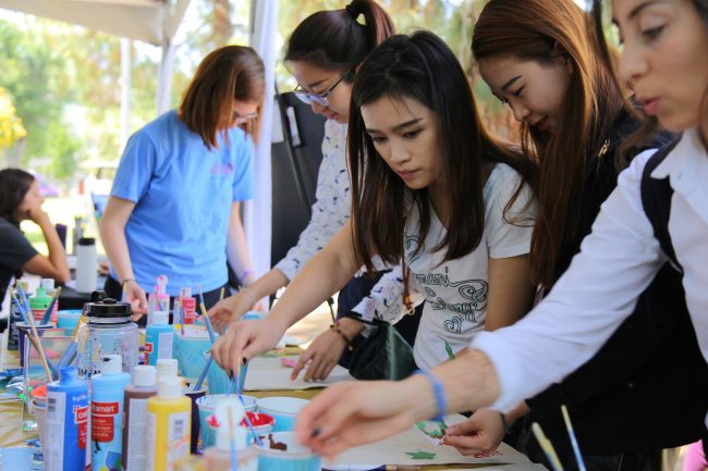 Students painting on bags that will be donated to local food banks at the Earth Fair on Thursday. (Magaly Barajas / The Sundial)