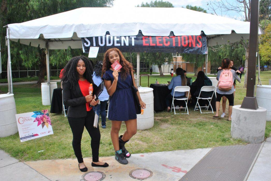 """Two students pose in front of """"Student Elections"""" banner"""