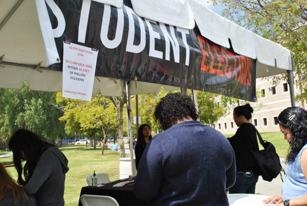 "Students stand in line at ""Student Election"" table"