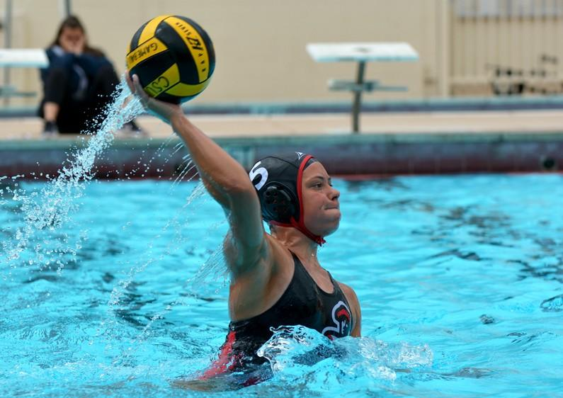 Water+polo+athlete+throws+ball+as+she+lifts+herself+above+water