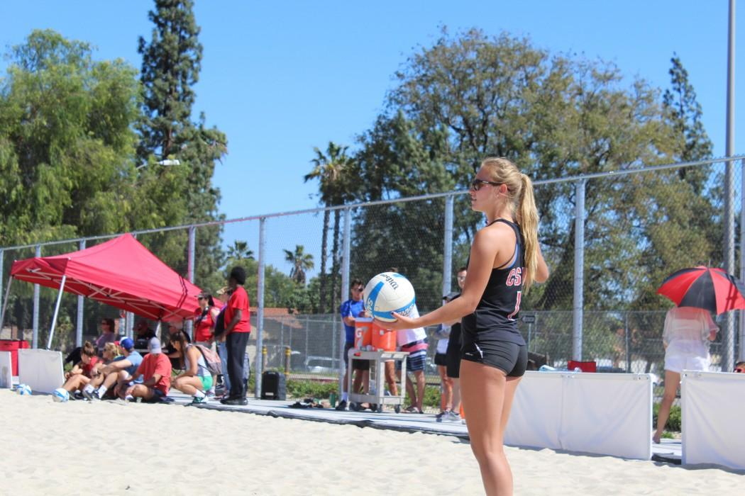 Student+athlete+stands+on+sand+during+volleyball+match