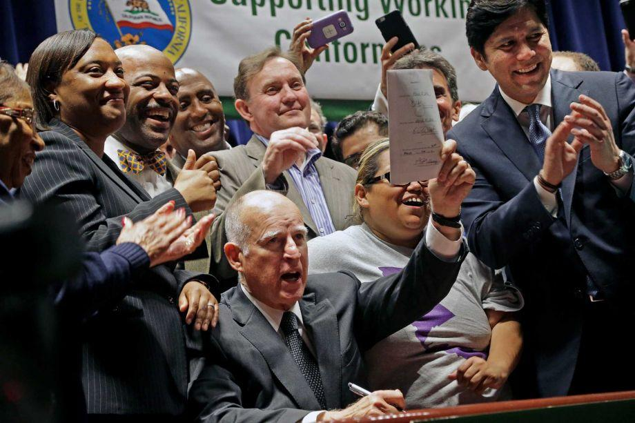 Government+members+stand+around+Jerry+Brown+holding+up+newly+signed+document