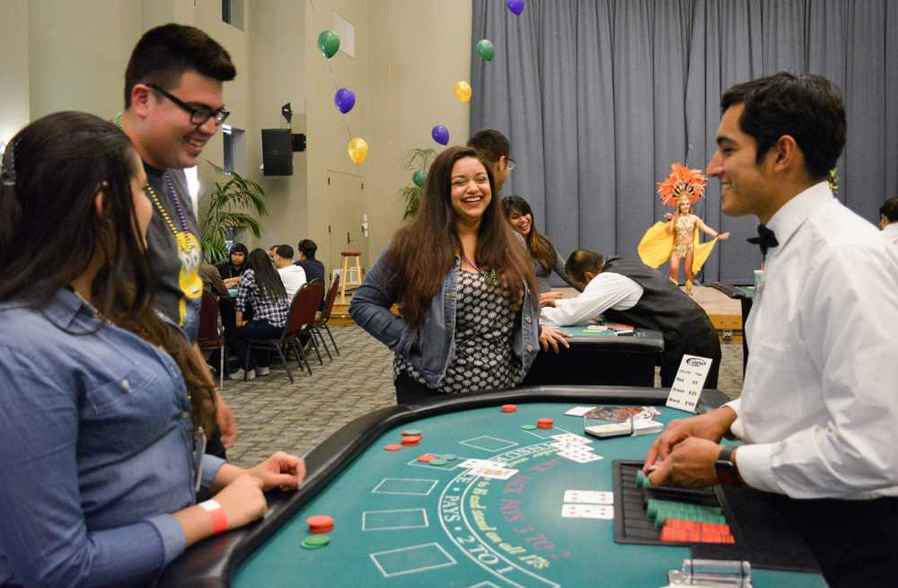 Several students play poker along table