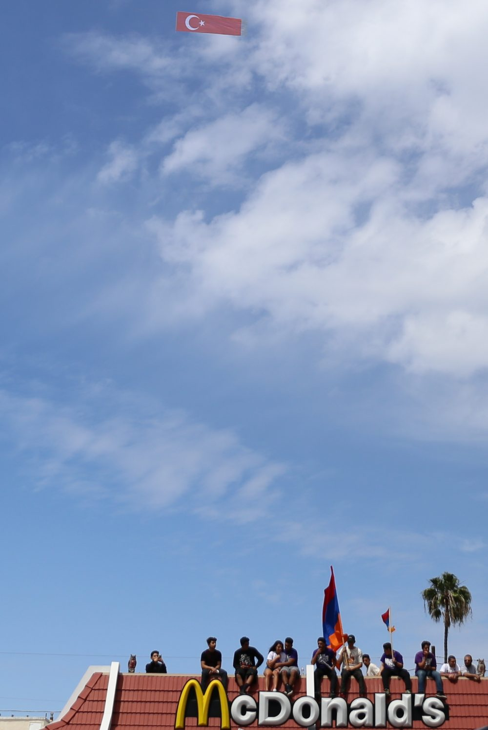 Protesters wave armenian flag while plane flies overhead with Turkish flag