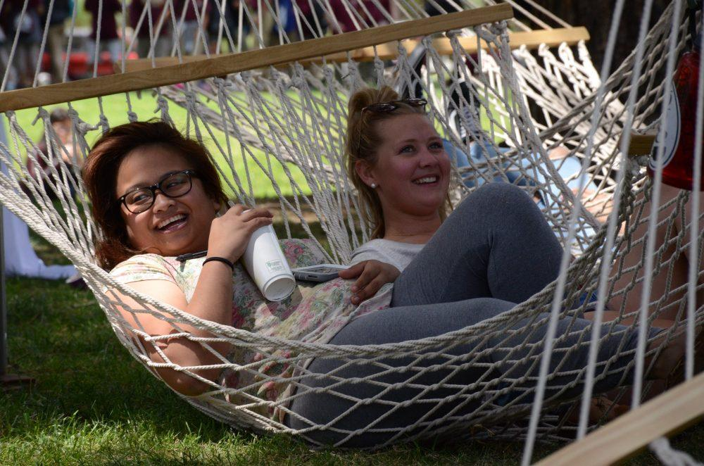 Two female students sit in a hammock together