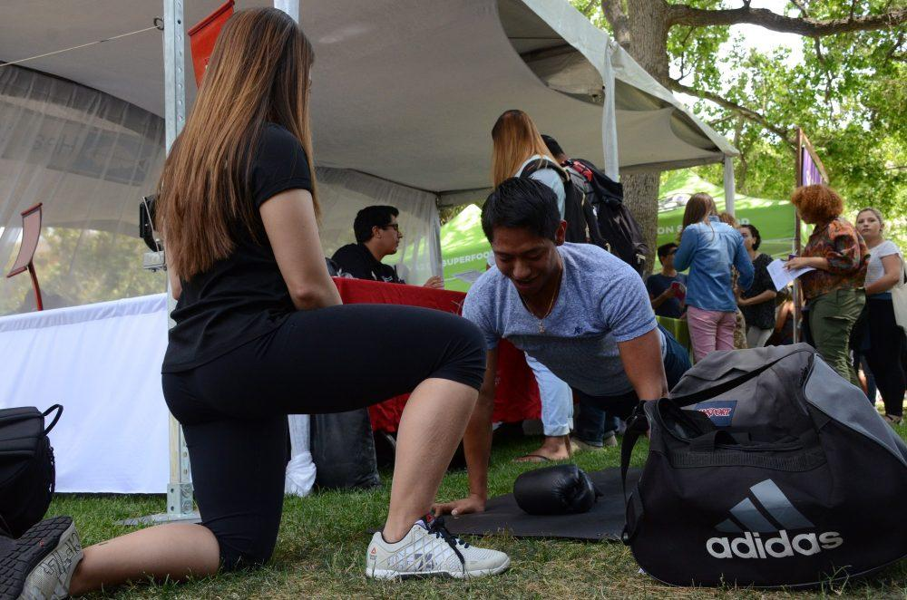 A student does push ups while another watches over him