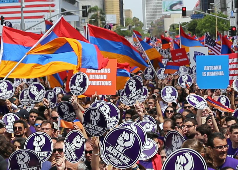 "Large crowd shows people waving flags and holding signs that say ""justice armenian genocide"""
