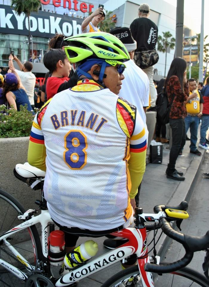 Man wears Kobe Bryant jersey on top of bicycle attire as he bikes