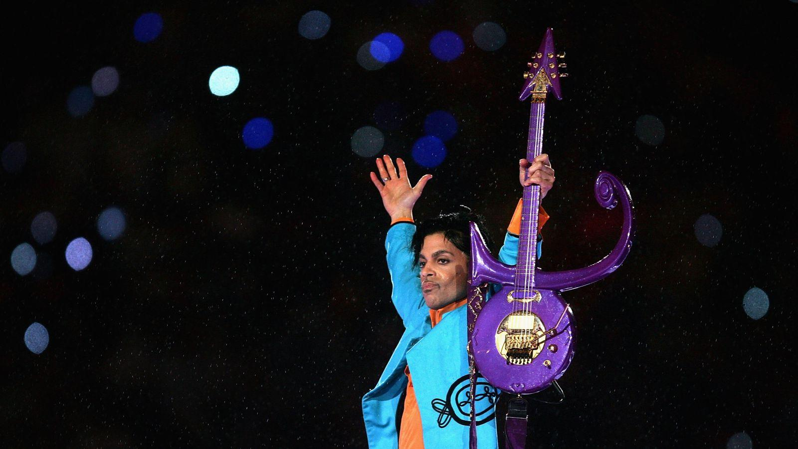 Price holds up purple guitar