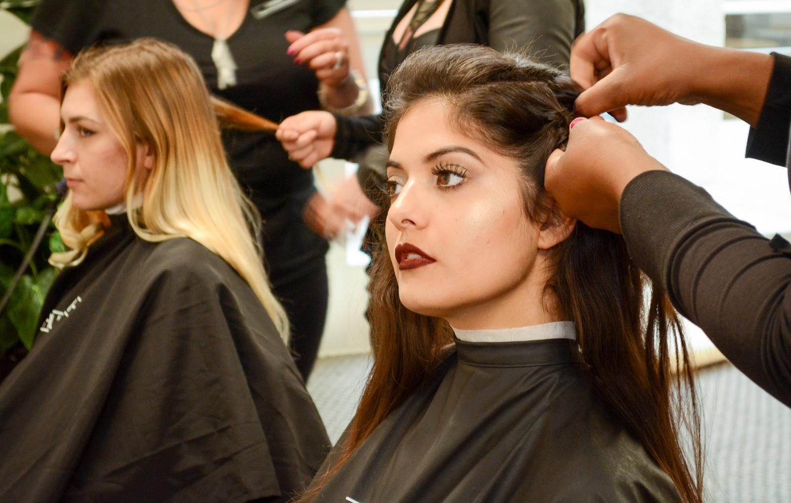 Models have their hair done before show