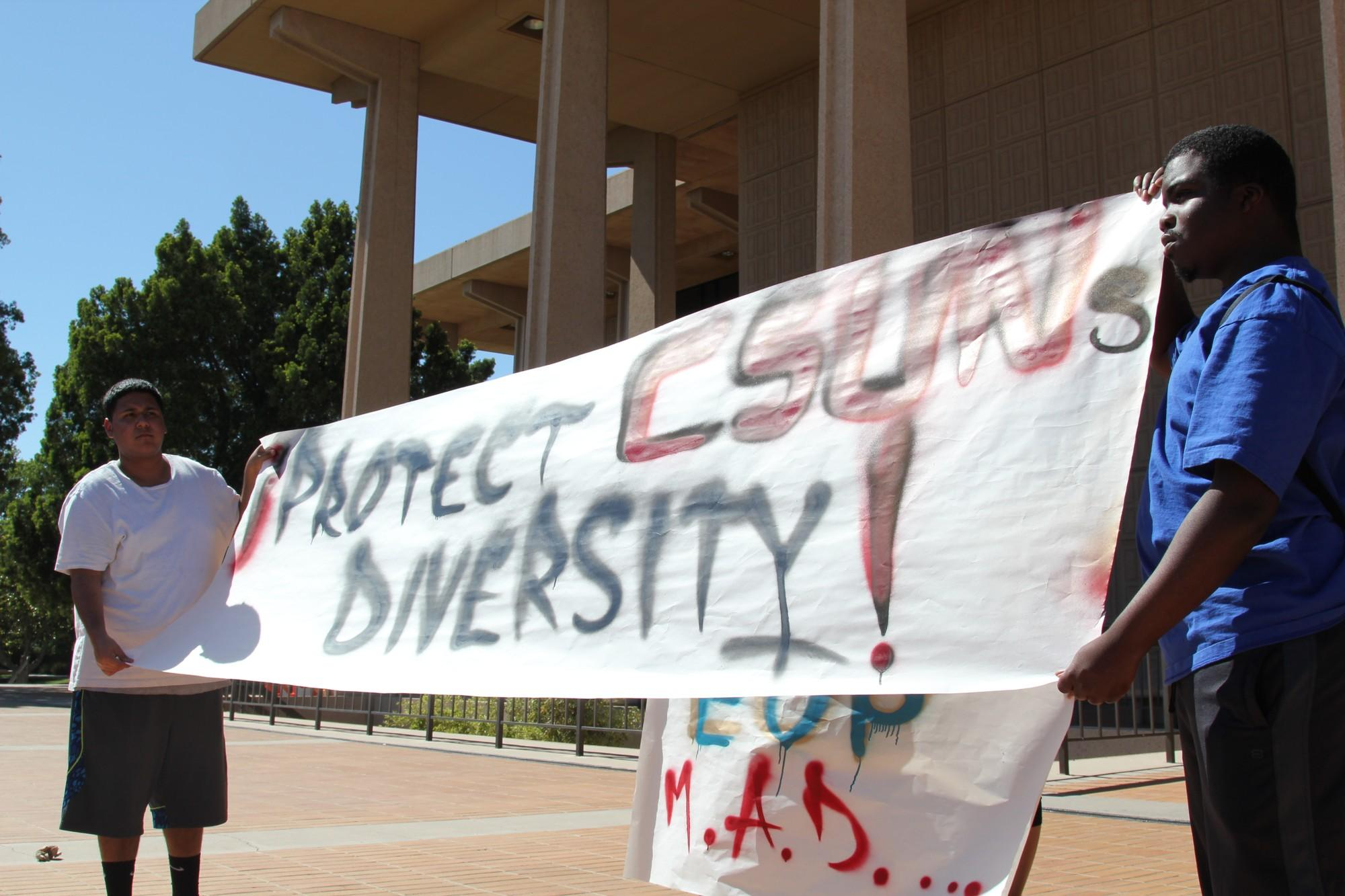"""students hold up sign that says, """"protect CSUN's diversity"""""""