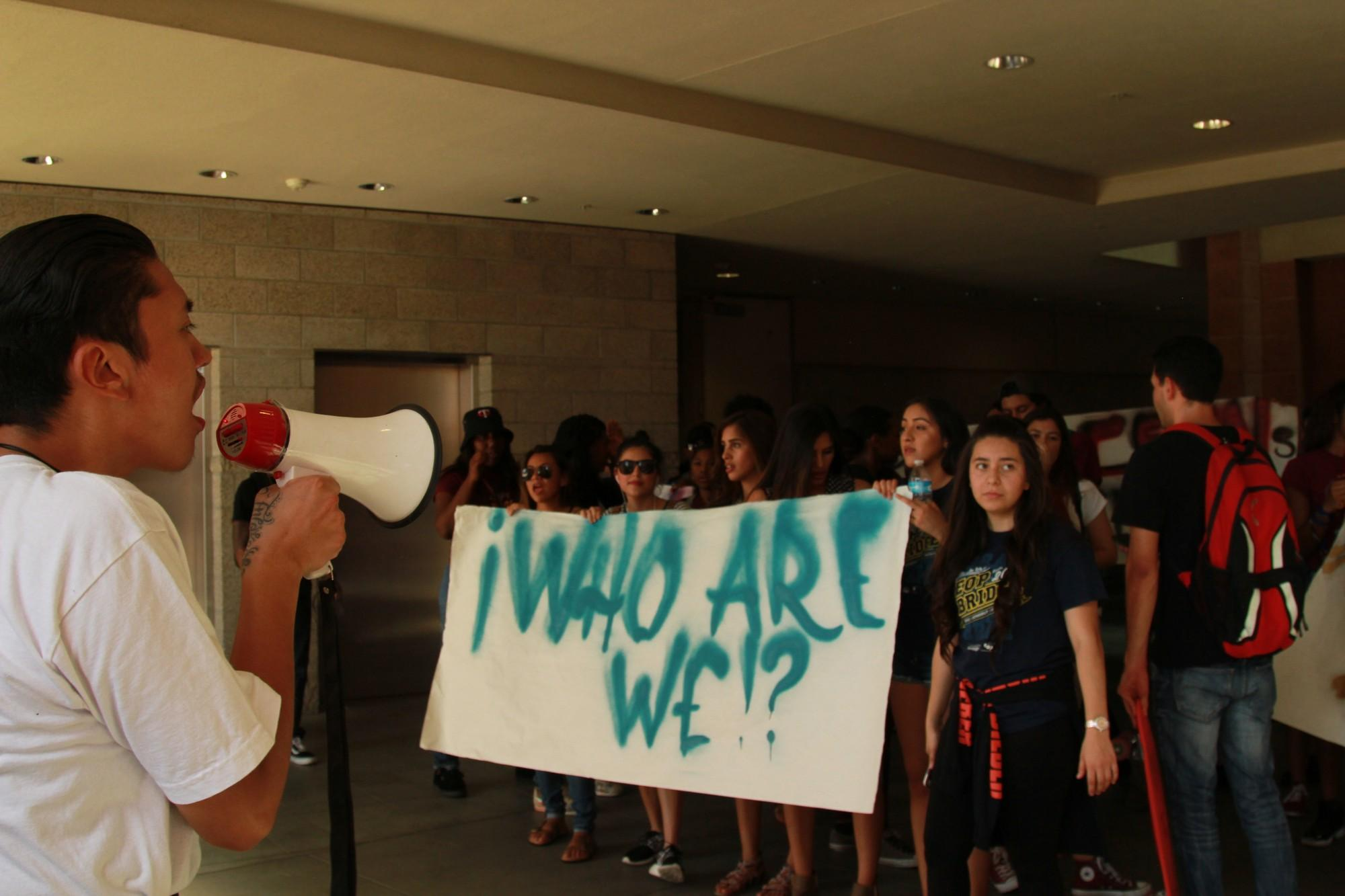 """Students hold up banner that says, """"Who are we"""""""