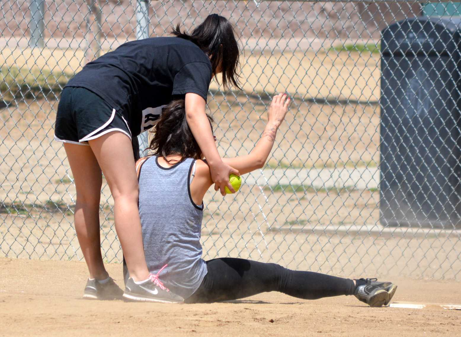 Jessica Kwack helps Tiffany Chen up after Chen slid to the base