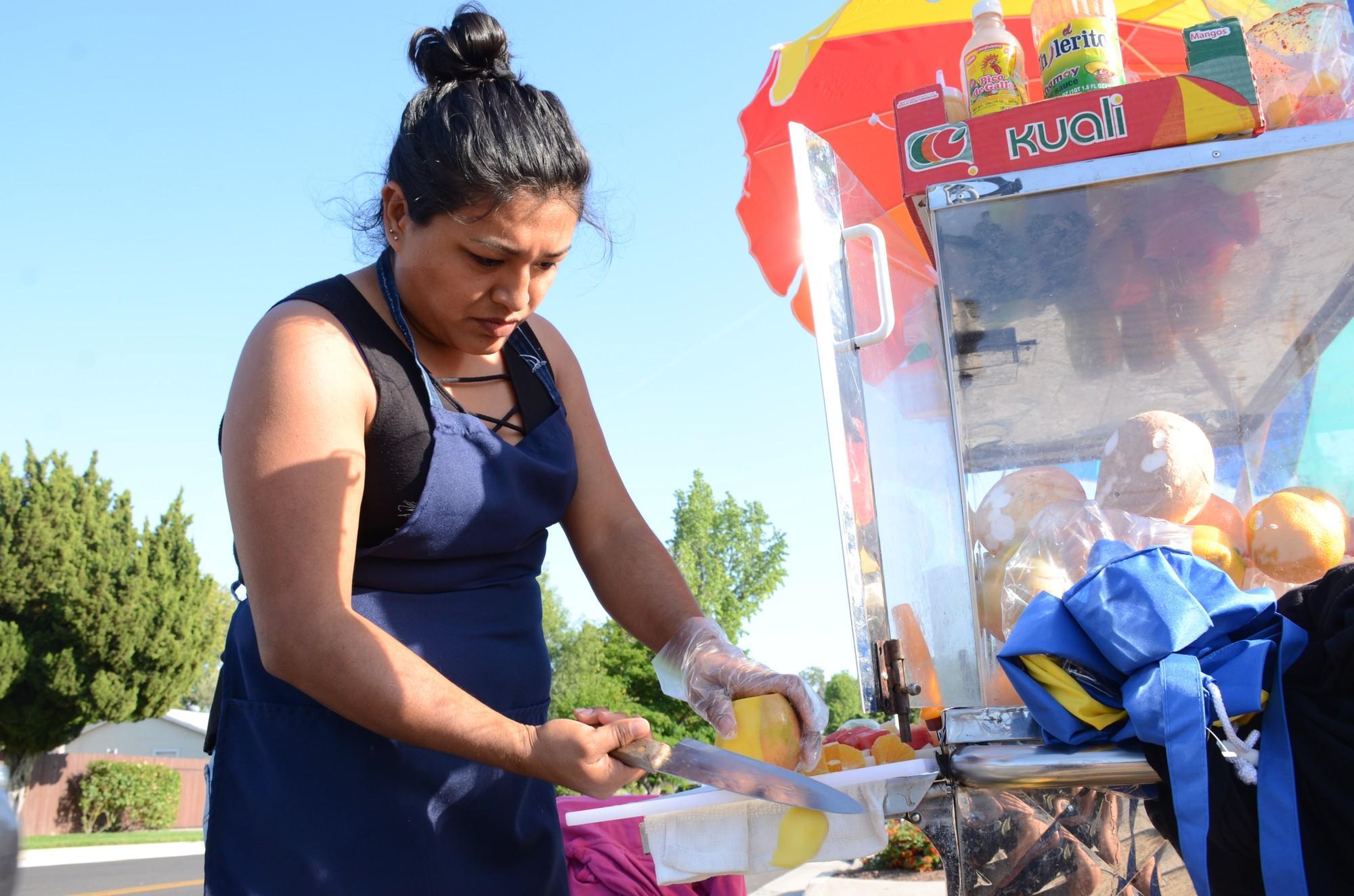 Woman peels mango