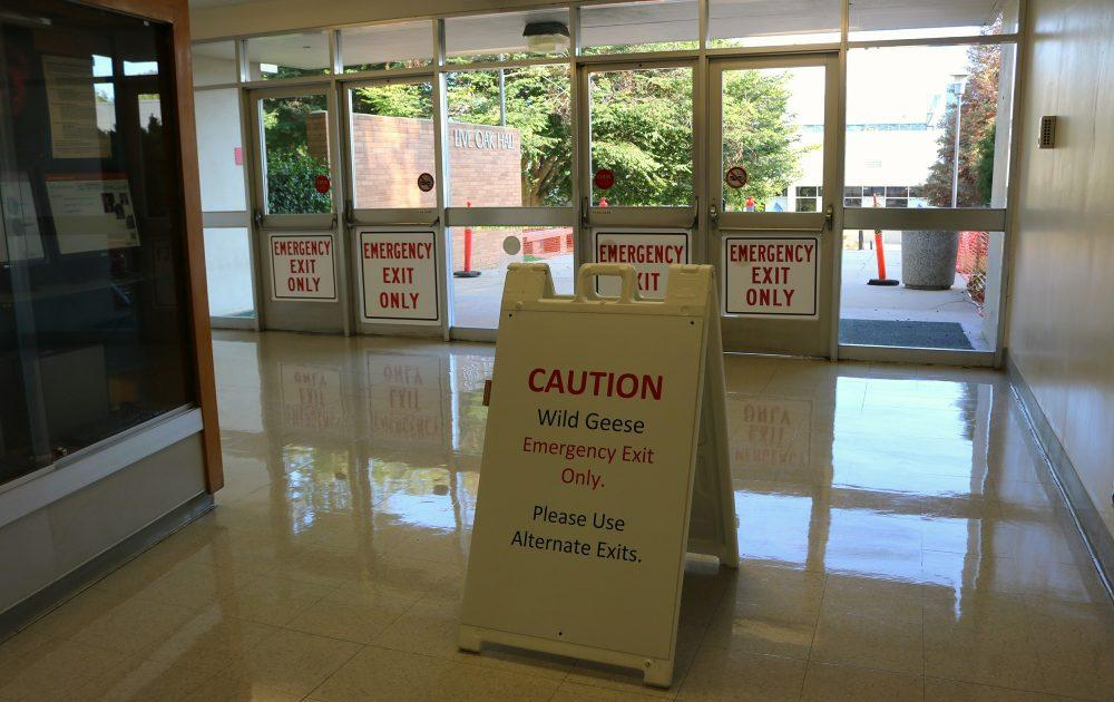 """Sign says, """"caution wild geese emergency exit only. please use alternate exits"""""""