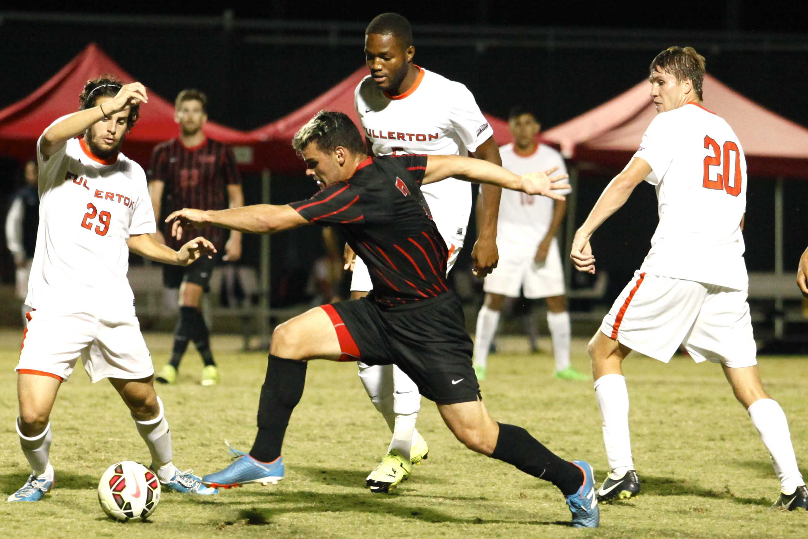 CSUN soccer player takes the ball from Fullerton player