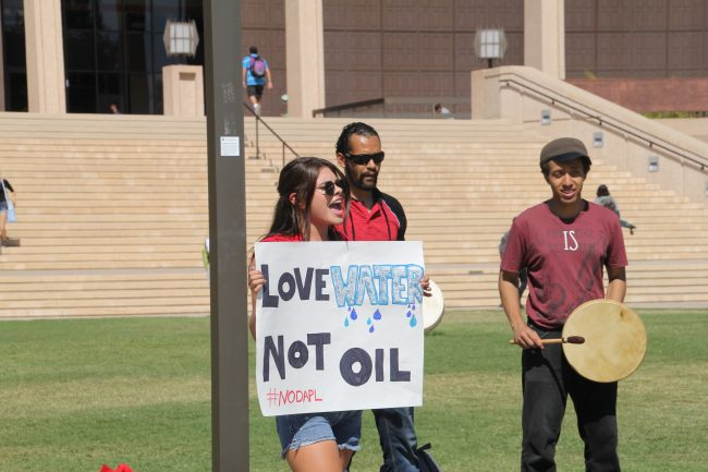 Kristen Littlecrow chants as Xavier Fierro (L) and Armond S. Handwick (R) play drums in protest to the ETP;s new pipeline.