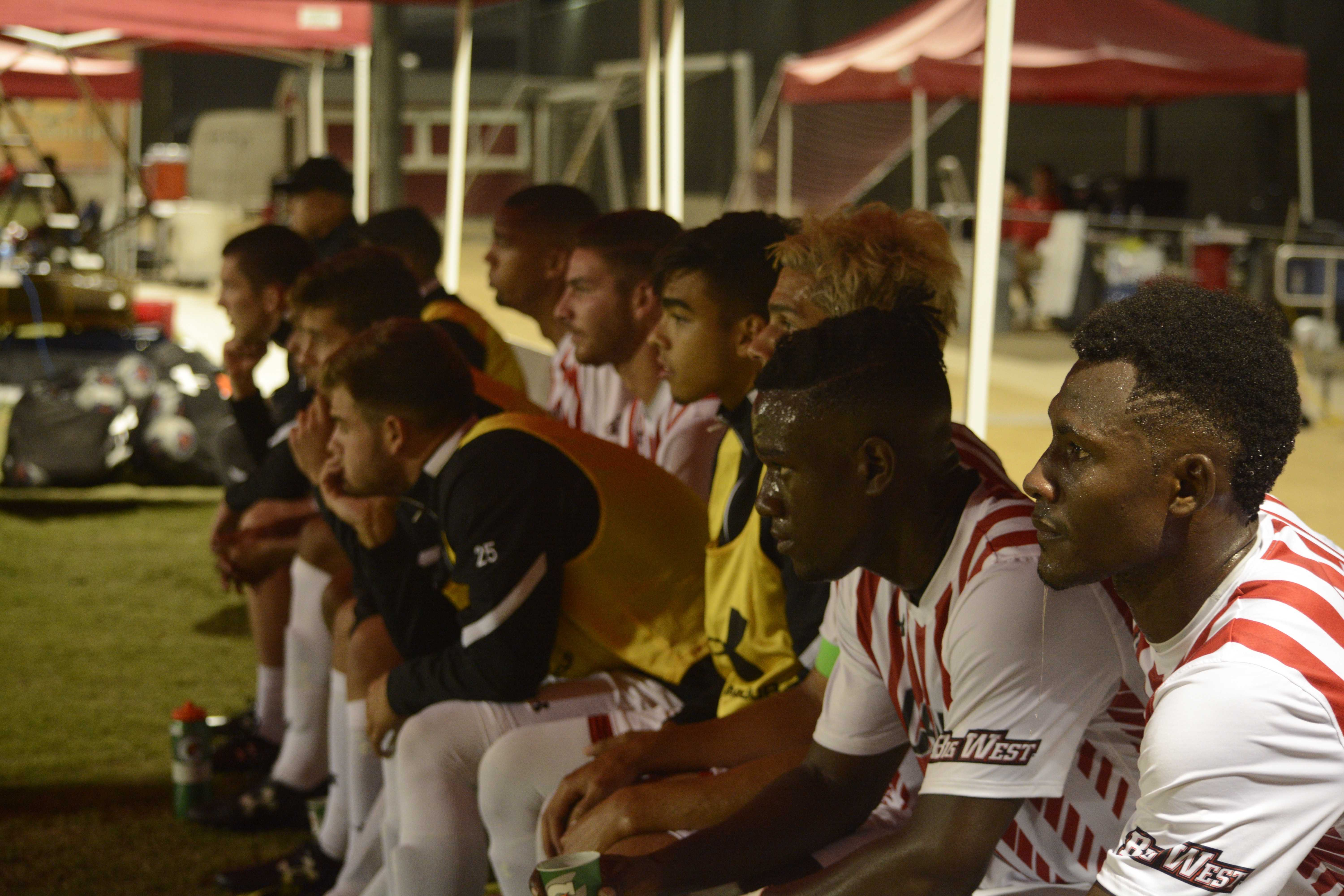 The men's soccer team watches their team from the bench
