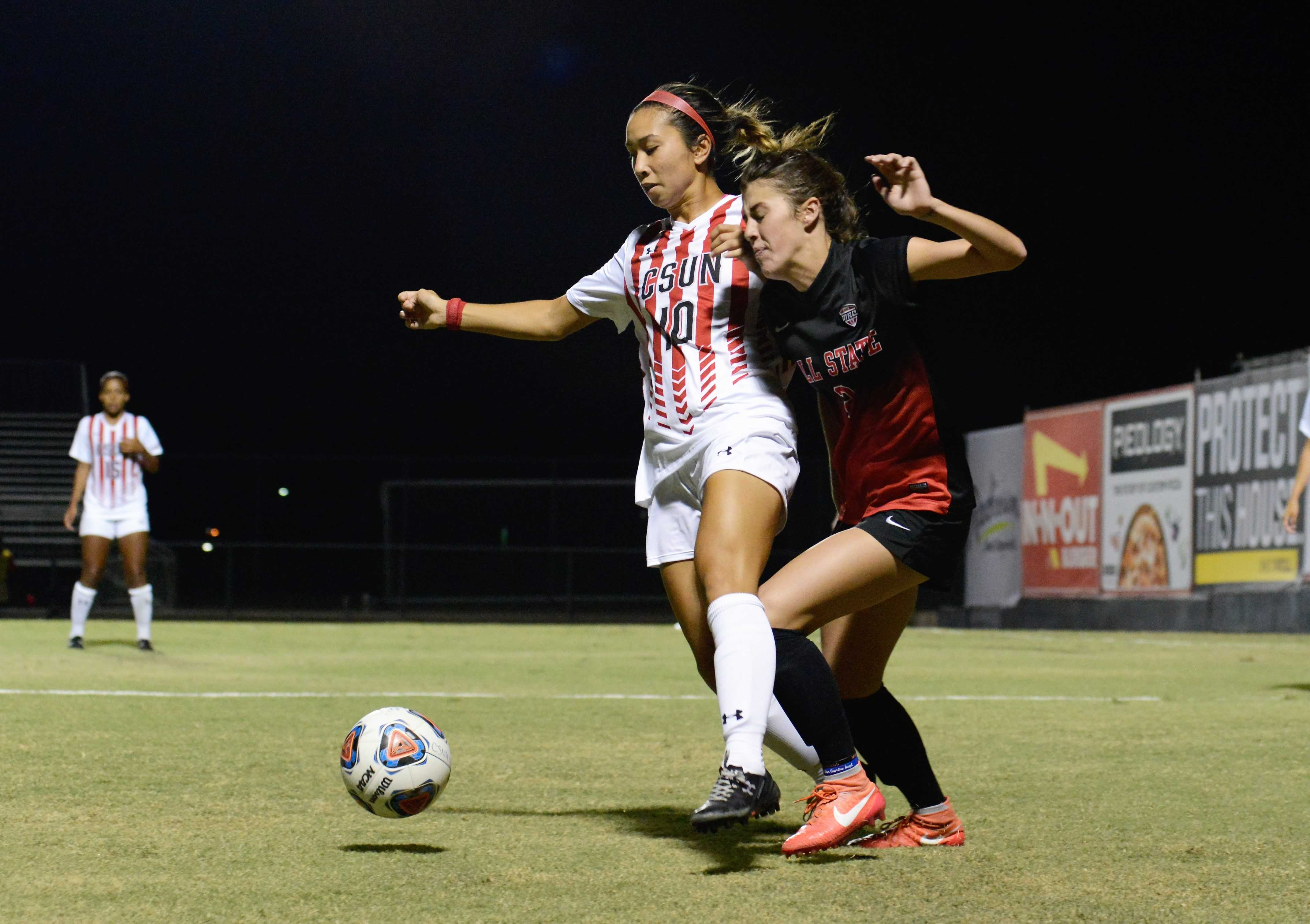 CSUn soccer player blocks opponent from the ball