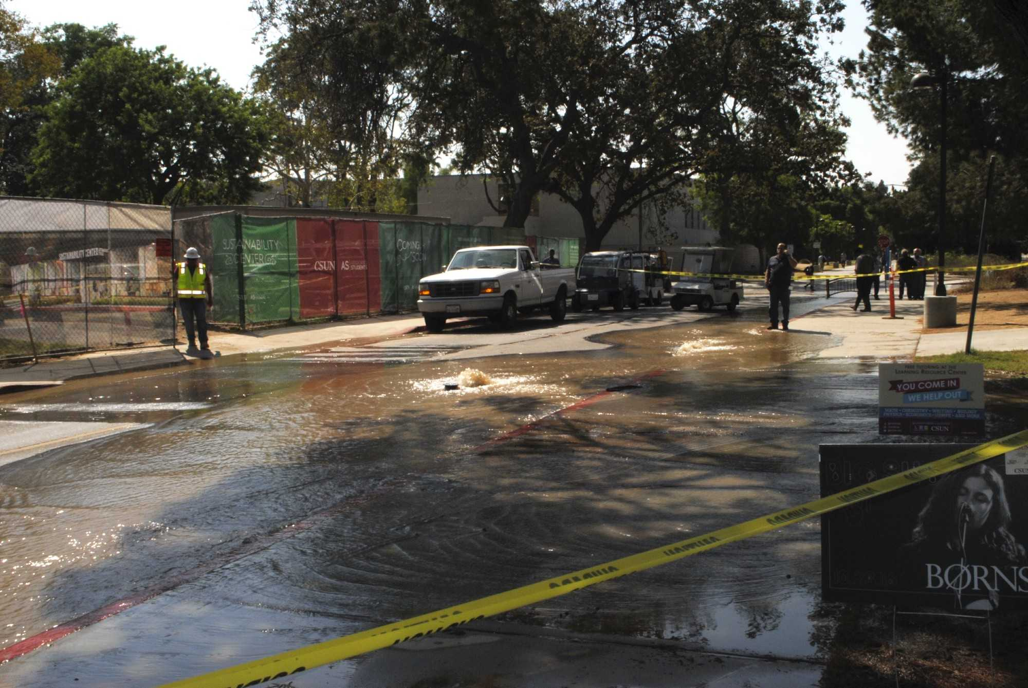 Water pours out of a water main behind he Matadome