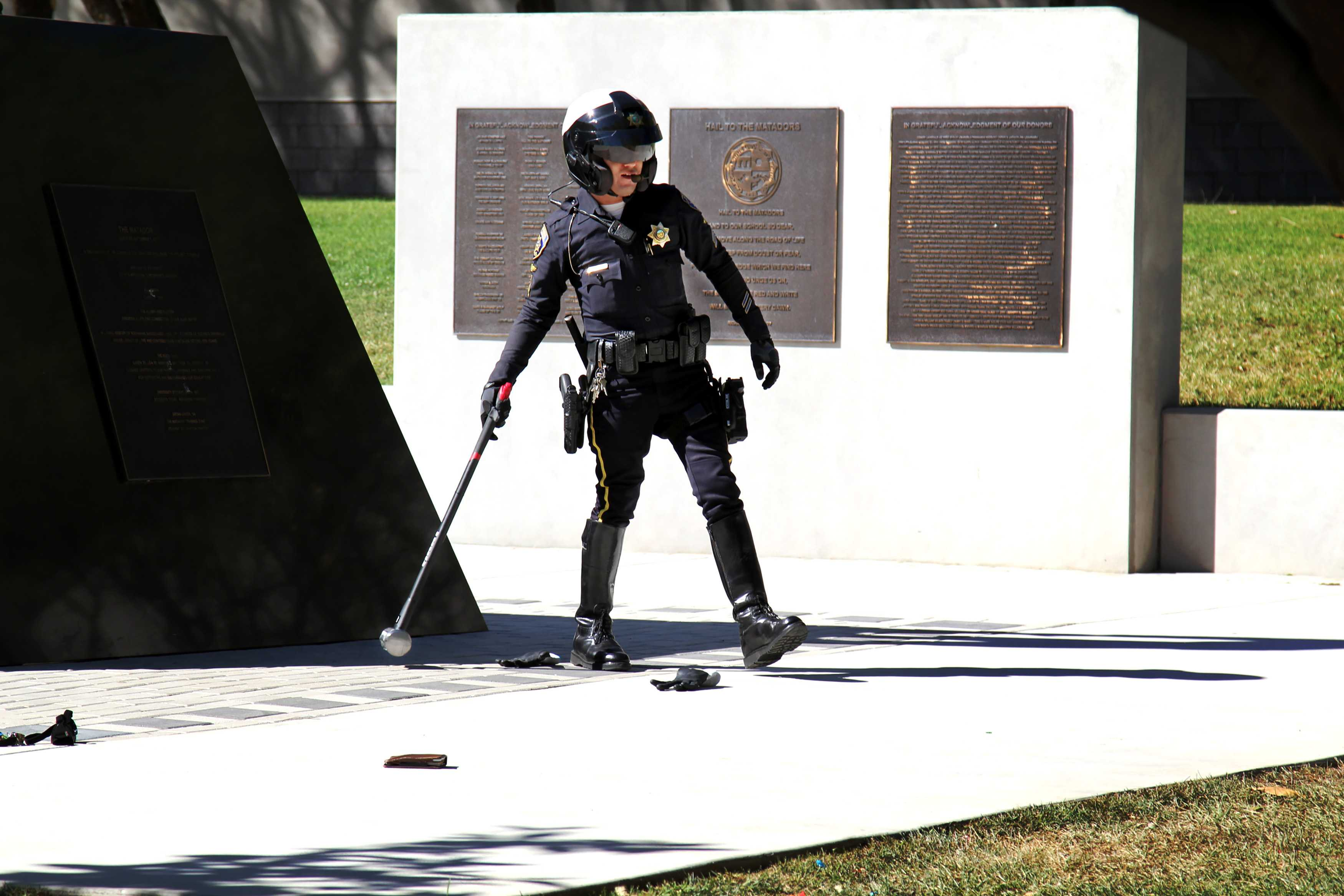 Police officer retrieves the sledge hammer used to damage school property